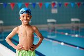 Portrait Of Boy Standing By Edge Of Swimming Pool Ready For Lesson poster
