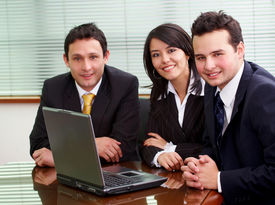 image of business meetings  - businessmen and businesswomen in a business meeting in an office smiling with a laptop on the table - JPG