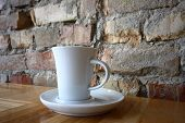 Coffee cup over a brick wall