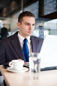 Businessman sitting at table in cafe using laptop computer