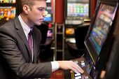 stock photo of gambler  - Young handsome men gambling in the casino on slot machines - JPG