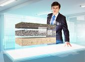 Image of young businessman looking at high-tech picture of topsoil