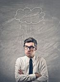 Worried office worker with a cloud drawn on a blackboard over his head