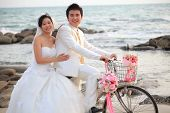 Couple Of Young Man And Woman In Wedding Suit Ridiing Old Bicycle On Sand Beach