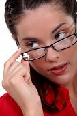 stock photo of risque  - Woman seductively removing glasses - JPG