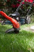 foto of electric trimmer  - Woman is trimming her lawn with electric edge trimmer - JPG