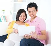 Asian couple. Husband and 8 months pregnant wife using tablet computer sitting on sofa at home