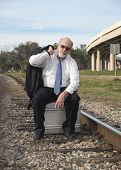 Jobless Senior Businessman Sits On Suitcase On Railroad Train Tracks