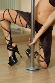 pic of lap dancing  - Young professional pole dancer exercising in the studio in strip plastic dance - JPG