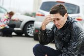 stock photo of wrecking  - Adult upset driver man in front of automobile crash car collision accident in city - JPG