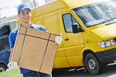 stock photo of movers  - Smiling young male postal delivery courier man in front of cargo van delivering package - JPG