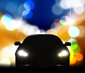 Silhouette of car with headlights against night traffic light background.