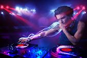 stock photo of laser beam  - Handsome disc jockey playing music with light beam effects on stage - JPG