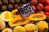 foto of pawpaw  - Display of fresh fruit on market stall in La Boqueria covered market - JPG