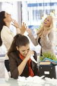 Fired female employee crying at desk, colleagues celebrating at the background.