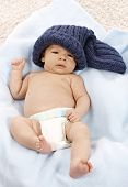 Lovely newborn baby wearing nappy and knitted cap.
