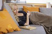 Attractive young woman lying on sofa, sleeping.