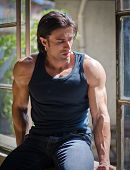 Handsome, Muscular Man Sitting On Open Window