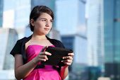 picture of bolero  - Beautiful girl in pink dress with tablet pc looks away near skyscrapers - JPG