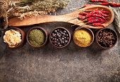 stock photo of chillies  - Various spices in wooden bowls on stone surface - JPG