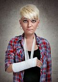 funny sad girl with holding her painful  broken arm