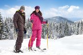 Young woman and man  skiers with ski equipment
