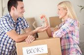 Couple moving into new home with door keys and boxes