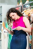 Young woman looking at expensive price tag while fashion shopping in boutique or store
