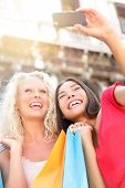 Girlfriends shopping laughing happy taking photo with smartphone. Woman friends holding shopping bag