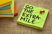 go the extra mile  - motivational reminder or procrastination concept  - handwriting on sticky note
