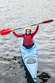 Happy woman in a kayak cheering at the camera in the middle of a lake