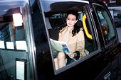 image of cabs  - Young woman reading newspaper inside taxi cab - JPG