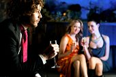 pic of flirtatious  - Charming beautiful girls looking at handsome young guy in a bar - JPG