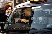 stock photo of cabs  - Taxi cab driver communicating with male passenger - JPG