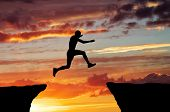 stock photo of gap  - Man jump through the gap on sunset fiery background - JPG