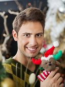 Portrait of handsome young man holding stuffed toy in Christmas store