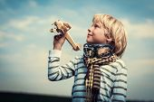 Smiling boy with wooden plane