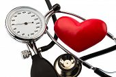 a blood pressure meter, a heart and stethoscope lying on a white background