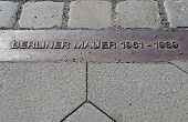 stock photo of tyranny  - Two rows of stones and this label on the streets of Berlin mark where the wall between east and west berlin used to be - JPG
