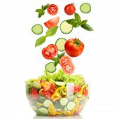 Fresh mixed vegetables falling into bowl of salad isolated on white