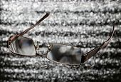 Eyeglass With Reflexion On A Brilliant Background