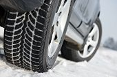 pic of snowy-road  - Car with winter tyres installed on light alloy wheels in snowy outdoors road - JPG