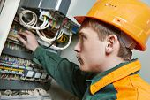 Young adult electrician builder engineer switching actuator equipment in distribution fuse box