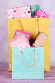 Presents in paper bags on table on bright background