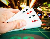 stock photo of poker hand  - poker cards in a man hand on green gaming table - JPG