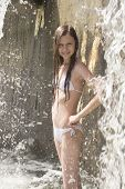 young girl under waterfall