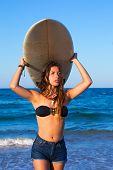 Brunette surfer teen girl holding surfboard in blue beach