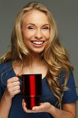 Positive young woman with long hair and blue eyes holding thermo mug