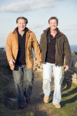 picture of gay couple  - A color portrait photo of a mature gay couple holding hands and laughing as they walk together during a day outdoors - JPG