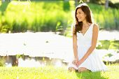 Asian woman sitting in park in spring or summer. Beautiful young woman smiling happy wearing white sundress sitting down in grass in park, Cute mixed race Asian Caucasian woman in her 20s.
